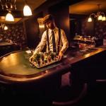 Ambiance casino clandestin, vous êtes à une table de Black Jack et le barmen prend la place du croupier