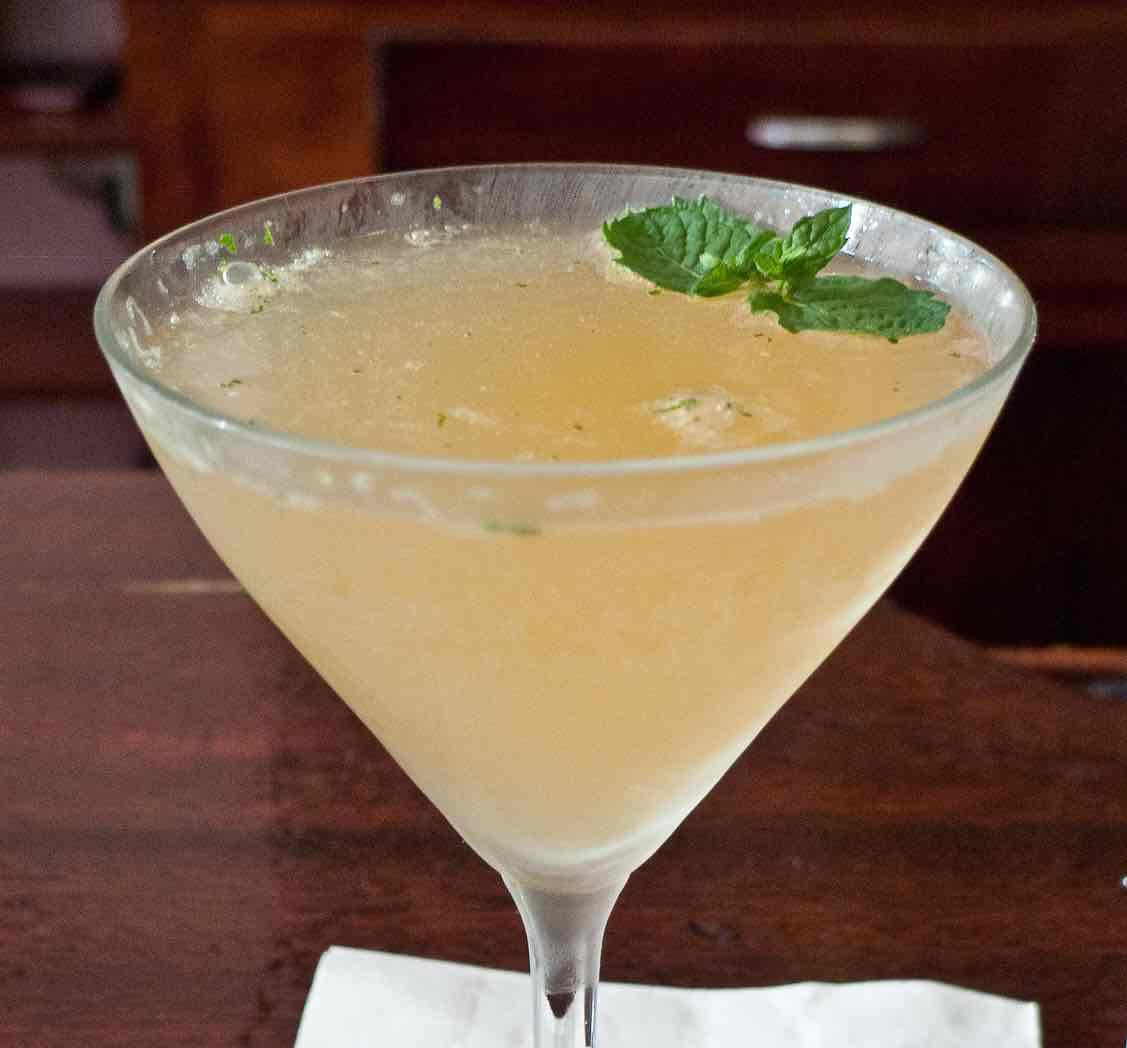 Old Cuban cocktail dans une coupe garni d'une feuille de menthe