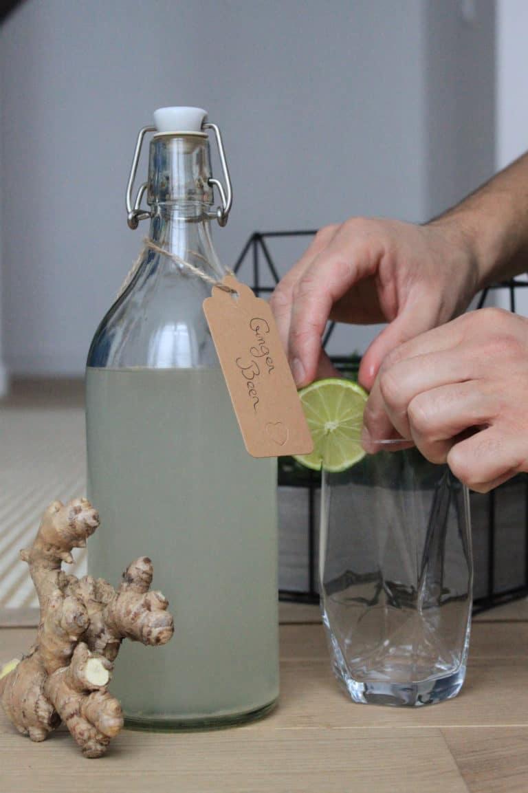 Une bouteille de ginger beer, du gingembre, et des mains qui mettent une rondelle de citron vert sur un verre