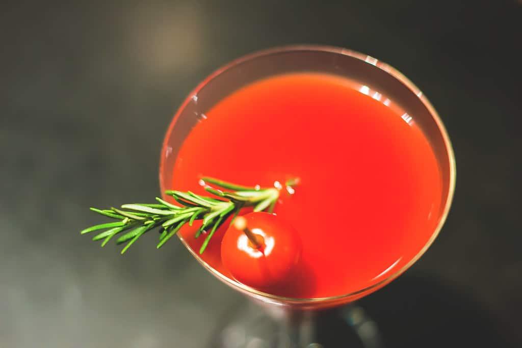 Un verre de bloody mary avec une branche de romarin et une tomate cerise en garnish