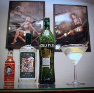 Un cocktail Dry Martini avec ses ingrédients : gin, vermouth sec et orange bitters