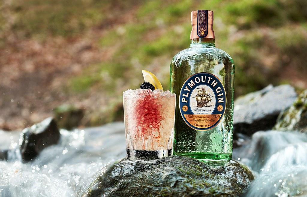 Un cocktail Bramble à côté d'une bouteille de Plymouth Gin