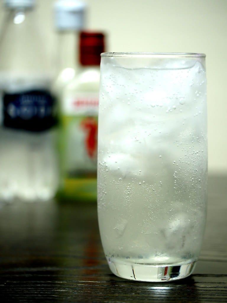 Un grand verre de Tom Collins avec une bouteille de soda water et de gin en arrière plan