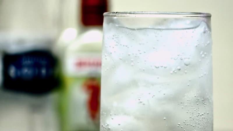 Gros plan sur un Tom Collins cocktail avec une bouteille de Gin Beefeater en fond