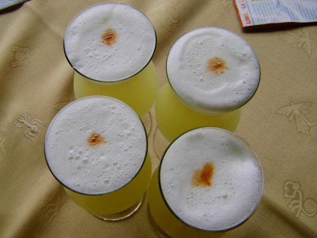 quatre pisco sours avec un trait d'angostura bitters