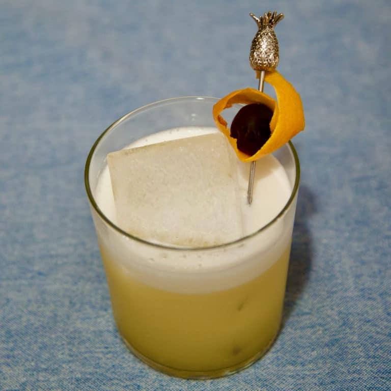 Un Amaretto Sour garni d'une cerise confite et d'un orange peel
