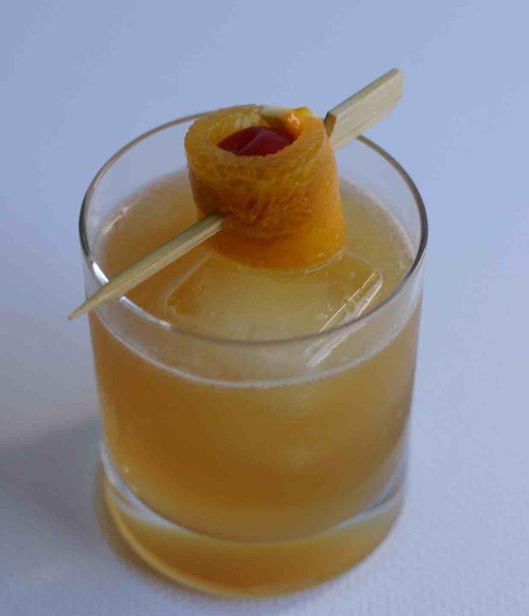 Un amaretto sour dans un verre rocks garni d'une cersie