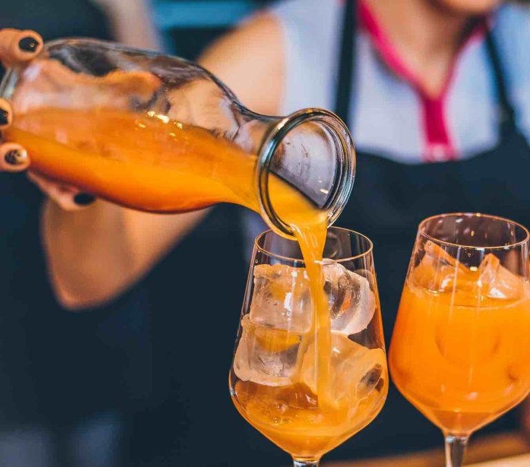 Un punch orange servi dans un verre à vin rempli de glaçons