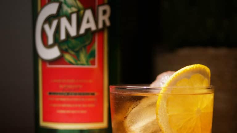 Un Cynar Spritz avec la bouteille de Cynar en fond