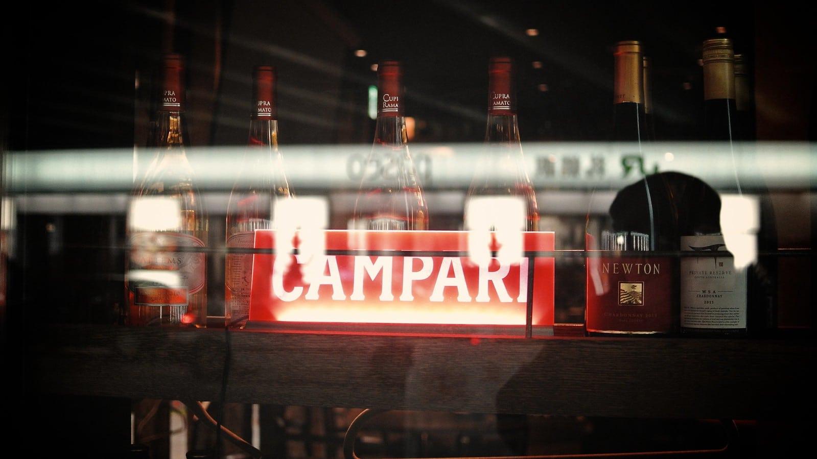 Une enseigne Campari reflétée dans une vitrine