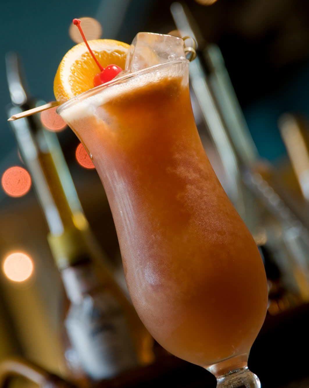 Un verre de cocktail Hurricane, garni dune tranche de citron et une cerise au marasquin mauvaise version)