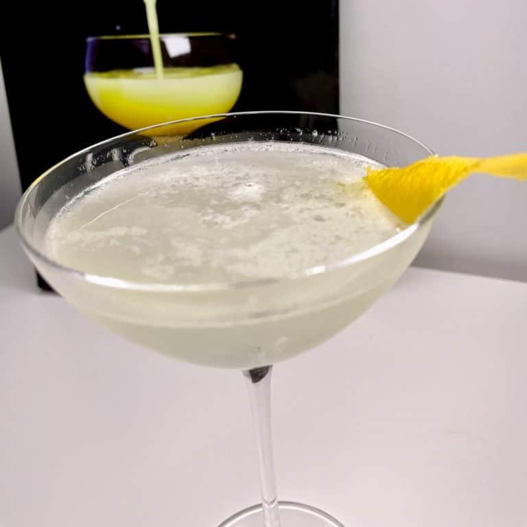 Un White Lady, garni d'un zeste de citron, un cocktail à base de gin, Cointreau et citron